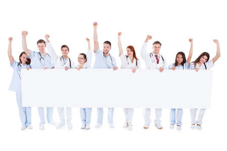Large diverse group of healthcare personnel standing in a line holding a blank white banner with copyspace and cheering raising their fists in the air isolated on white photo