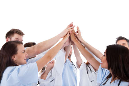 round: Large group of motivated doctors and nurses standing in a circle giving a high fives gesture with their hands meeting in the centre  conceptual of teamwork isolated on white Stock Photo