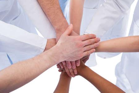 grupo de médicos: Los médicos y enfermeras de apilamiento manos. Aislados en blanco