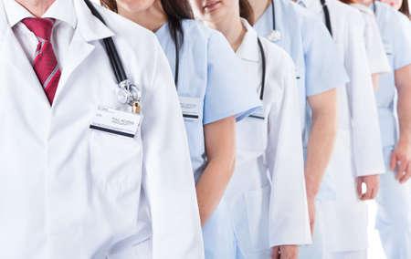 grupo de doctores: Largo retroceso de la l�nea o cola de m�dicos sonriendo y enfermeras con uniformes blancos que usan estetoscopios alrededor del cuello aislados en blanco