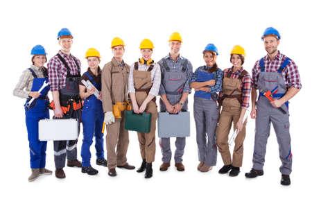 Large group of diverse workmen and women standing in a row holding their tools and equipment and wearing hardhats  isolated on white photo
