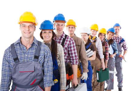 constructor: Gran grupo de trabajadores de la construcci�n u obreros y mujeres haciendo cola en una larga fila llevando sus juegos de herramientas, ya que esperar al reloj en o ser contratados para un trabajo aislado en blanco