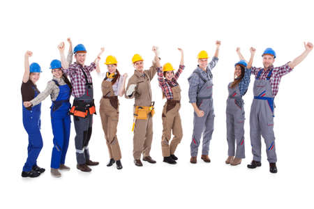 artisan: Large group of diverse multiethnic cheering artisans in dungarees and hardhats with toolbelt standing in a line isolated on white Stock Photo