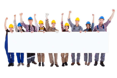 Group of diverse skilled motivated workmen and women standing in a line cheering celebrating a success holding a blank white banner with copyspace for your text on a white background photo