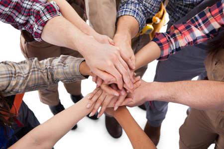 comercio: Gran grupo de trabajador de la construcción de apilamiento manos. Aislados en blanco