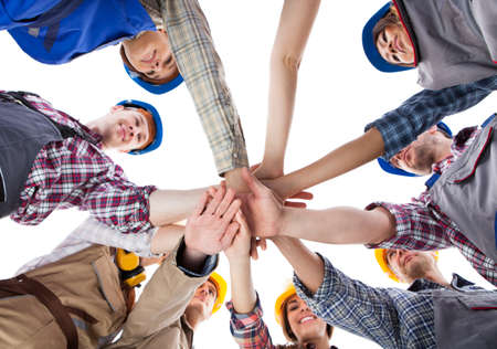 join: Large group of construction worker stacking hands. Isolated on white