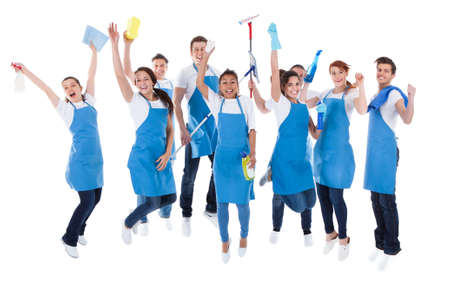 cleaning background: Large excited group of diverse multiethnic janitors jumping and cheering as they celebrate together as a team isolated on white Stock Photo