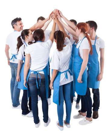 Cleaning team: Group of cleaners making high five gesture. Isolated on white