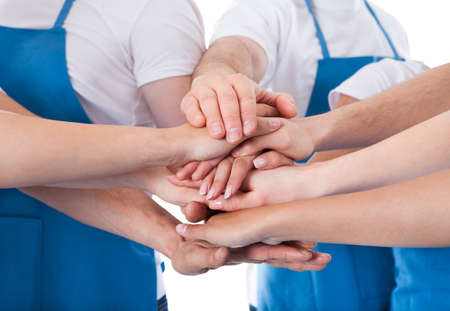 Low angle view of cleaners stacking hands over white background photo