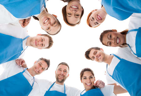 Large group of cleaners standing in circle. Isolated on white photo