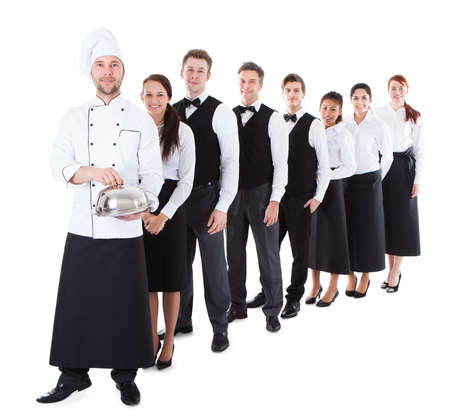Large group of waiters and waitresses standing in row. Isolated on white photo