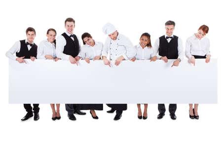 cocinero: Gran grupo de personal de la cocina, con un cartel en blanco con copyspace para el texto que incluye una anfitriona camareros camareras de chef y sumiller aislado en blanco