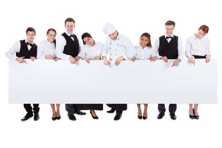Large group of catering staff holding a blank banner with copyspace for your text including a chef  waiters  waitresses  hostess and wine steward  isolated on white Фото со стока
