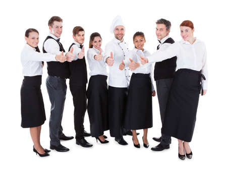 Waiters and waitresses showing thumbs up sign. Isolated on white background photo