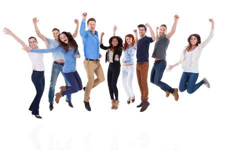Gruppo di persone diverse alzando le braccia e saltare. Isolati su bianco