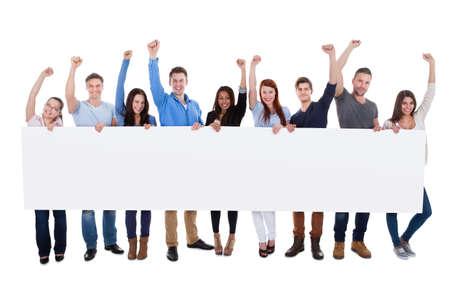 vzrušený: Nadšený skupina různorodých lidí drží banner. Samostatný na bílé
