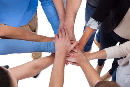 Group of people stacking hands together. Isolated on white photo