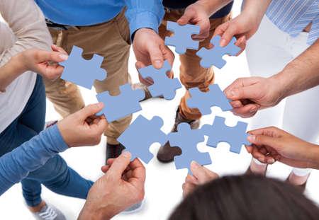 Hoge hoek van mensen verbinden puzzelstukjes op witte achtergrond Stockfoto