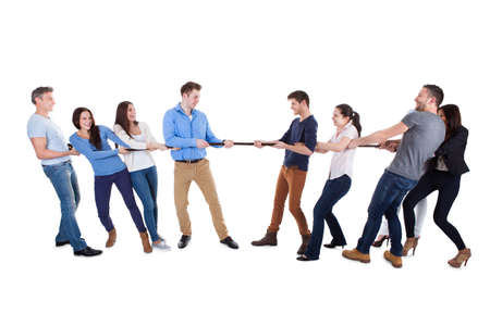 pulling rope: Two opposing teams having a tug of war pulling on opposite ends of a rope in a display of strength conceptual of competition  challenge and determination  on white Stock Photo