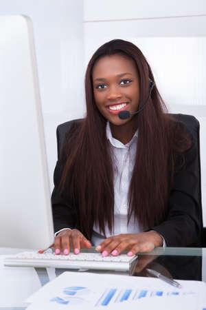 Portrait of confident customer service representative working at desk in office photo