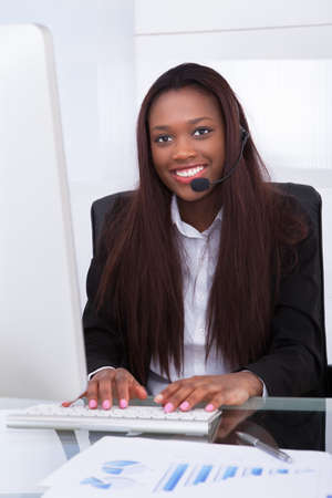 up service: Portrait of confident customer service representative working at desk in office Stock Photo