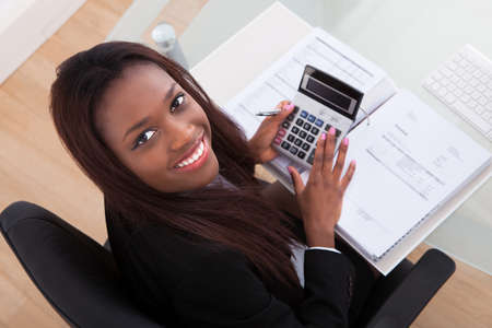tax: Portrait of confident businesswoman calculating tax at desk in office Stock Photo