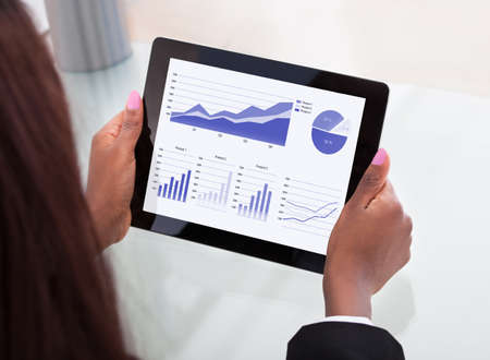 Cropped image of businesswoman analyzing financial charts on digital tablet at desk in office photo