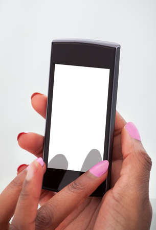Cropped image of businesswomans hands using mobile phone in office photo