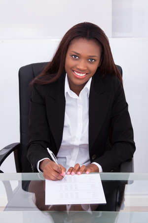 Portrait of confident businesswoman filling form at desk in office photo