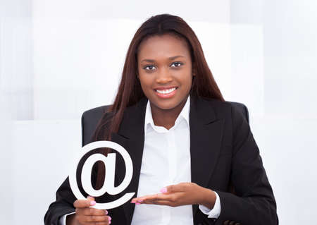 woman computer: Portrait of confident businesswoman holding at sign in office Stock Photo
