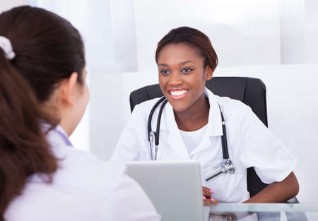 doctor laptop: Happy female dentist talking to patient at desk in clinic