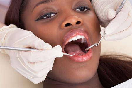 Nahaufnahme der weiblichen Patienten, die von Zahnarzt in der Klinik überprüft