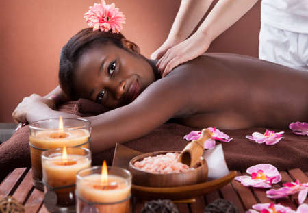 Side view of young woman receiving shoulder massage at spa salon Stock Photo