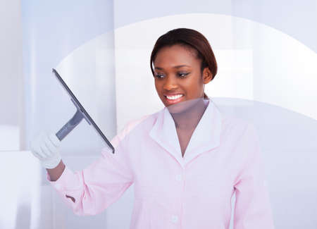 Smiling African American housekeeper cleaning glass in hotel photo