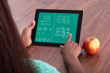 elearning: Cropped image of female student solving math problems on digital tablet at classroom desk Stock Photo