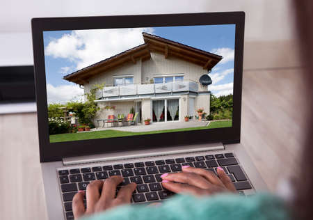 Cropped image of African American woman selecting new house on laptop at home