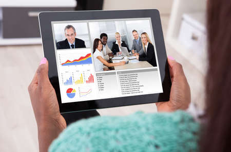 Webinar: Cropped image of African American businesswoman video conferencing with colleagues from home Stock Photo