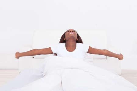 femme bouche ouverte: Portrait de jeune femme afro-am�ricaine qui s'�tend dans le lit � la maison Banque d'images