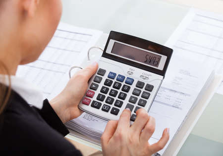Close-up Of Businesswoman Calculating Bills Using Calculator photo