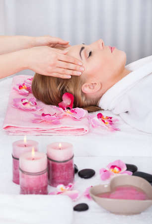 Young Woman With Eyes Closed Getting Head Massage From Masseuse photo