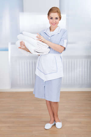 Portrait Of Happy Young Maid Holding Towels photo