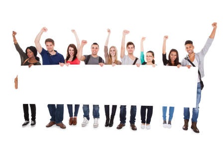 sign university: Full length portrait of successful college students displaying blank billboard against white background