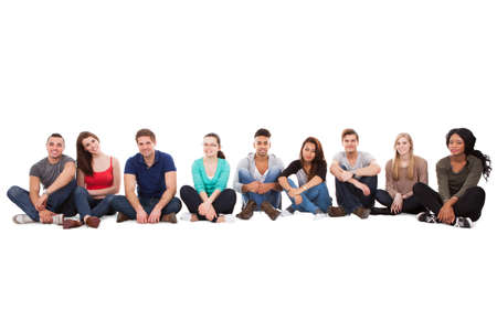 hispanic students: Full length portrait of multiethnic college students sitting in a row against white background Stock Photo