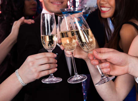 celebration party: Cropped image of friends toasting champagne flutes at nightclub Stock Photo