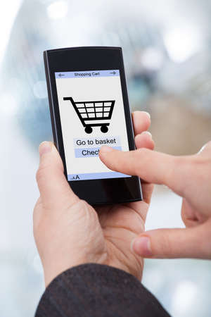 Cropped image of businesswomans hands using smartphone with online shopping application on screen photo
