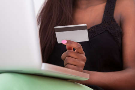 Close-up Of African American woman holding credit card while shopping online at home photo