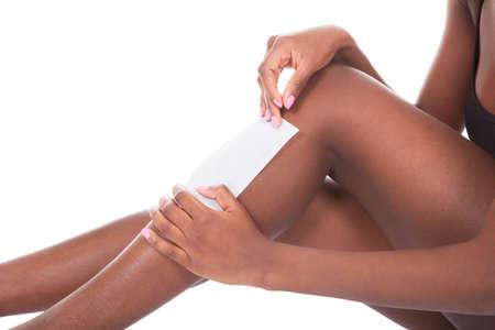 depilacion con cera: Joven mujer afroamericana depilación piernas contra el fondo blanco Foto de archivo