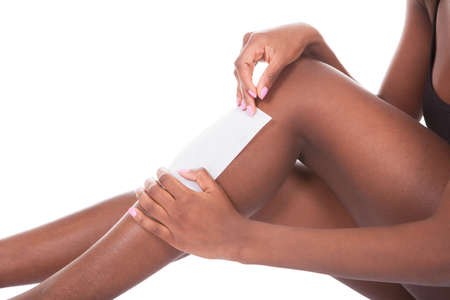 Young African American woman waxing legs against white background photo