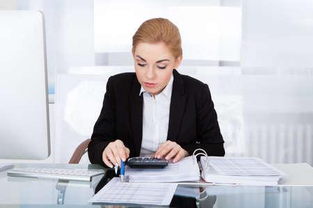 Portrait Of Young Businesswoman Calculating Bills Using Calculator photo