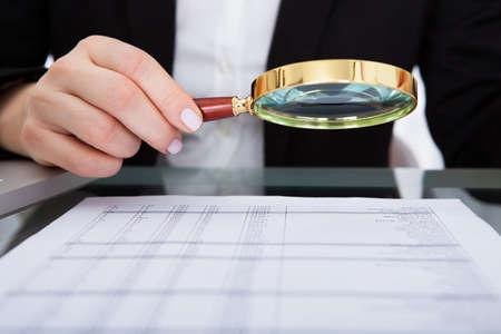 Üzletasszony nézett dokumentumot keresztül nagyító